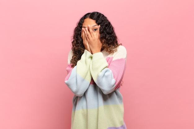 Giovane donna ispanica che si sente spaventata o imbarazzata, sbircia o spia con gli occhi semicoperti dalle mani