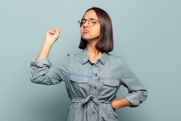 Giovane donna ispanica che si sente seria, forte e ribelle, alza il pugno, protesta o combatte per la rivoluzione