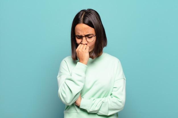 Giovane donna ispanica che si sente seria, premurosa e preoccupata, fissando di lato con la mano premuta contro il mento