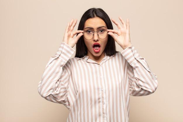 Giovane donna ispanica che si sente scioccata, stupita e sorpresa, con in mano gli occhiali con uno sguardo stupito e incredulo
