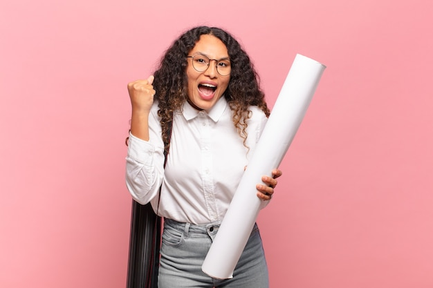 Giovane donna ispanica che si sente scioccata, eccitata e felice, ride e celebra il successo, dicendo wow !. concetto di architetto