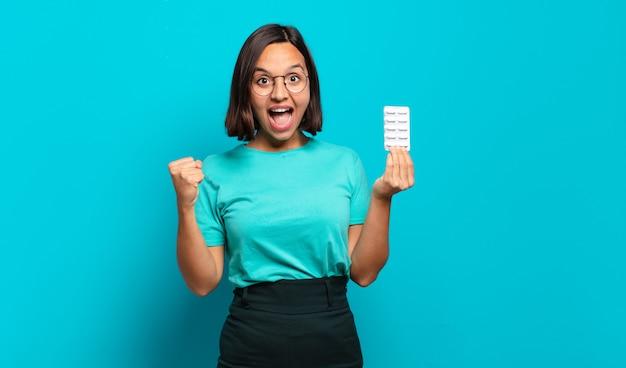 Giovane donna ispanica che si sente scioccata, eccitata e felice, ridendo e celebrando il successo, dicendo wow!
