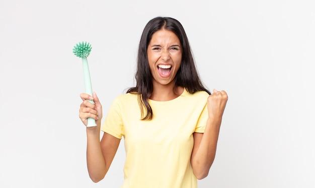 Giovane donna ispanica che si sente scioccata, ride e celebra il successo e tiene in mano una spazzola per la pulizia dei piatti