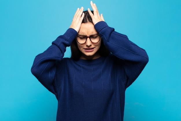 Giovane donna ispanica che si sente stressata e ansiosa, depressa e frustrata con un mal di testa, alzando entrambe le mani alla testa