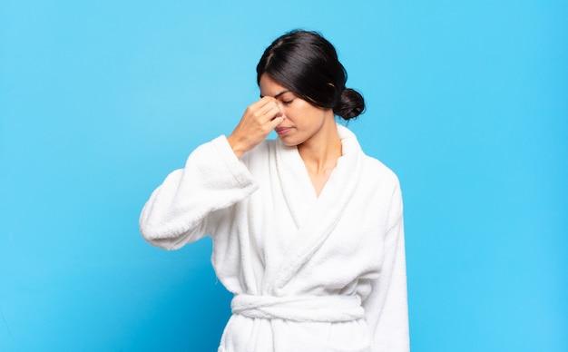 Giovane donna ispanica che si sente stressata, infelice e frustrata, tocca la fronte e soffre di emicrania di forte mal di testa. concetto di accappatoio