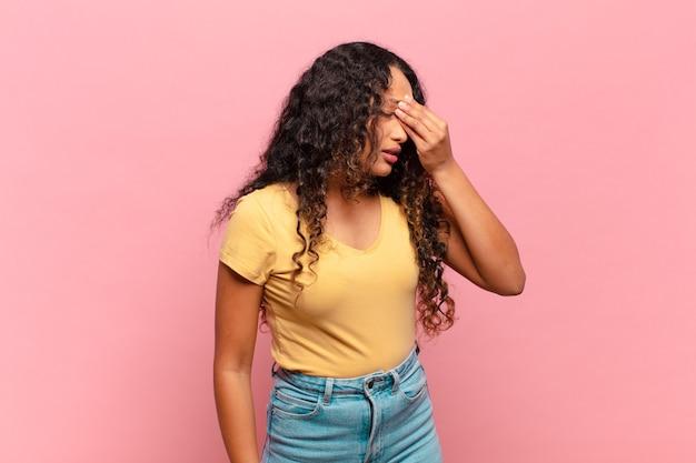 Giovane donna ispanica che si sente stressata, infelice e frustrata, tocca la fronte e soffre di emicrania di forte mal di testa