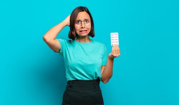 Giovane donna ispanica che si sente stressata, preoccupata, ansiosa o spaventata, con le mani sulla testa, in preda al panico per errore