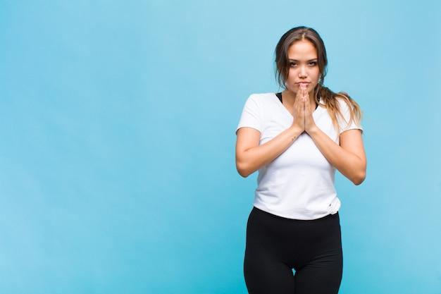 Giovane donna ispanica che si sente preoccupata, piena di speranza e religiosa, prega fedelmente con i palmi premuti, chiedendo perdono