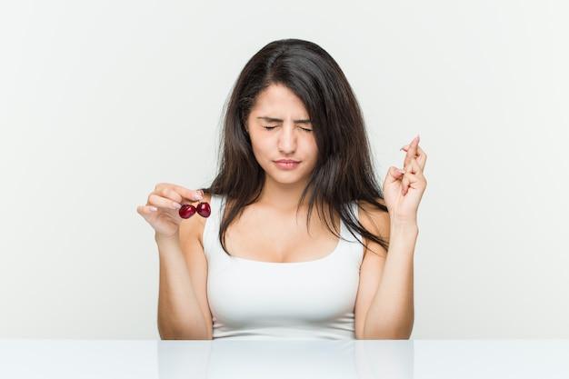 Ciliegie ispaniche della tenuta della giovane donna che incrociano le dita per avere fortuna