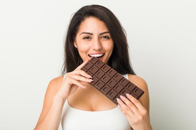 Giovane donna ispanica che tiene una compressa di cioccolato
