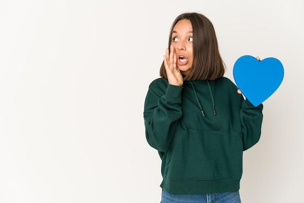 La giovane donna ispanica che tiene una figura del cuore sta dicendo una notizia di frenata calda segreta e sta guardando da parte