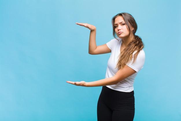 Giovane donna ispanica che tiene un oggetto con entrambe le mani sullo spazio della copia laterale, mostrando, offrendo o pubblicizzando un oggetto