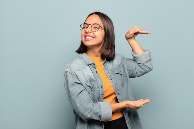 Giovane donna ispanica che tiene un oggetto con entrambe le mani sullo spazio laterale della copia, mostrando, offrendo o pubblicizzando un oggetto