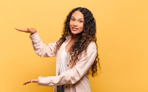 Giovane donna ispanica che tiene un oggetto con entrambe le mani sullo spazio della copia laterale, mostrando
