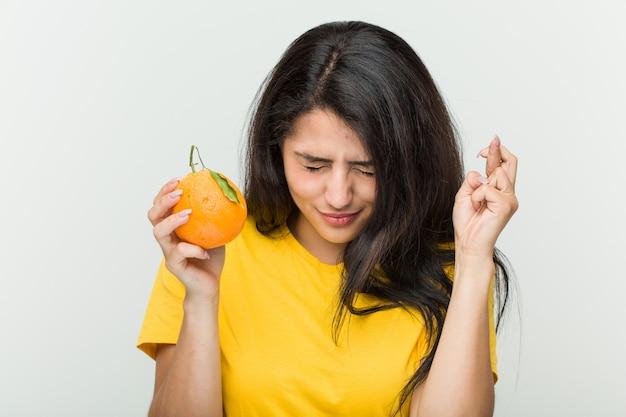 Giovane donna ispanica che tiene le dita di un incrocio arancio per avere fortuna