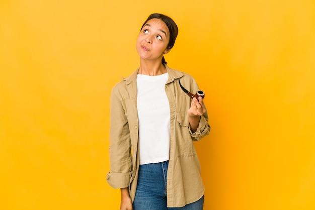 Giovane donna ispanica che tiene un tubo di fumo che sogna di raggiungere obiettivi e scopi