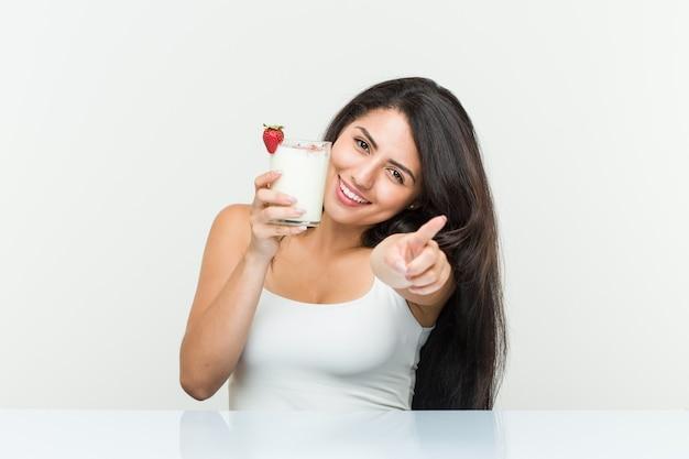Giovane donna ispanica con in mano un frullato giovane donna ispanica con in mano un toast di avocado sorrisi allegri che puntano in avanti. <mixto> Foto Premium
