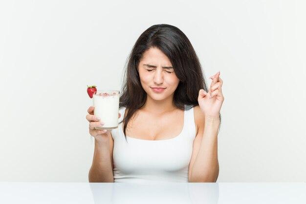 Giovane donna ispanica in possesso di un frullato giovane donna ispanica in possesso di un avocado toast dita incrociate per avere fortuna