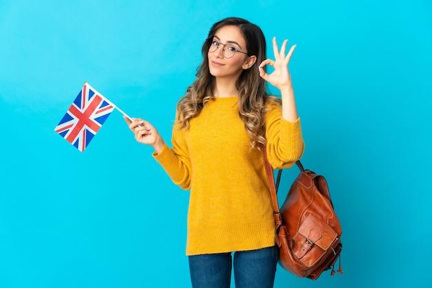 Giovane donna ispanica che tiene una bandiera del regno unito isolata sulla parete blu che mostra segno giusto con le dita