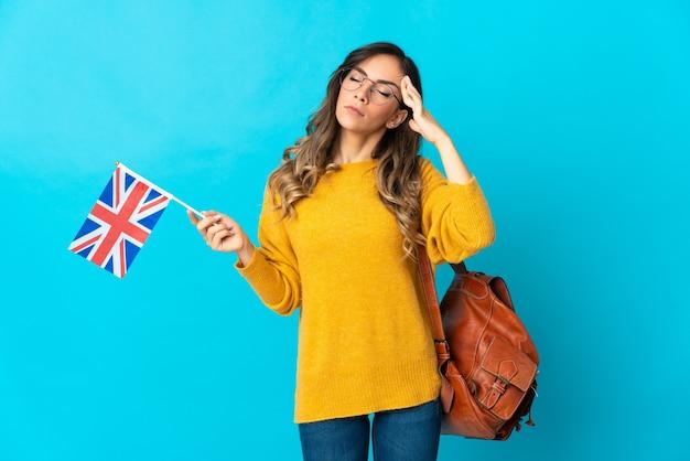 Giovane donna ispanica che tiene una bandiera del regno unito isolata sulla parete blu con mal di testa
