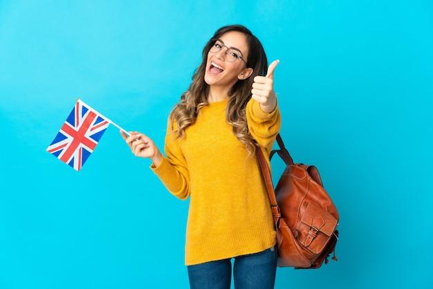 Giovane donna ispanica che tiene una bandiera del regno unito isolata sulla parete blu con i pollici in su perché è successo qualcosa di buono