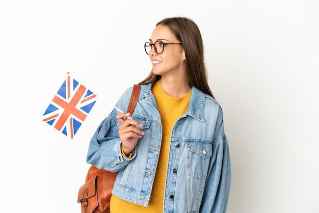Giovane donna ispanica che tiene una bandiera del regno unito su sfondo bianco isolato guardando side