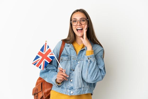 Giovane donna ispanica in possesso di una bandiera del regno unito su sfondo bianco isolato gridando con la bocca spalancata