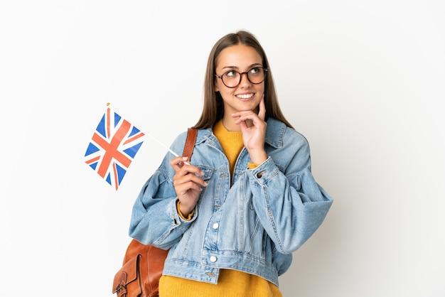 Giovane donna ispanica che tiene una bandiera del regno unito sopra fondo bianco isolato che pensa un'idea mentre osserva in su