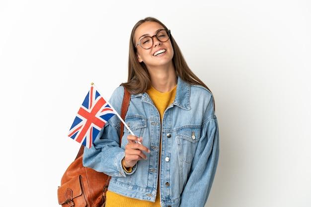 Giovane donna ispanica che tiene una bandiera del regno unito sopra la risata bianca isolata della parete