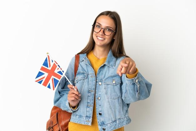 Giovane donna ispanica che tiene una bandiera del regno unito sopra la parete bianca isolata che indica la parte anteriore con l'espressione felice