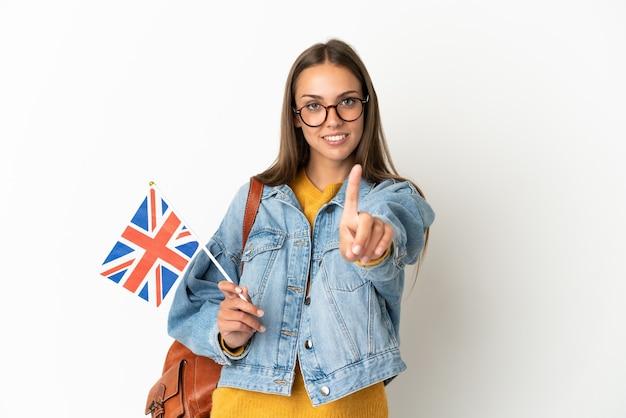 Giovane donna ispanica che tiene una bandiera del regno unito sopra la mostra bianca isolata della parete e che solleva un dito