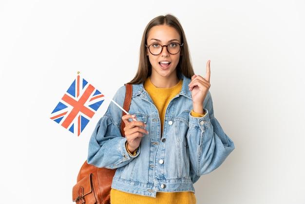 Giovane donna ispanica che tiene una bandiera del regno unito sopra il muro bianco isolato pensando un'idea che punta il dito verso l'alto