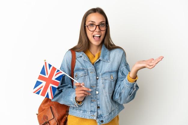 Giovane donna ispanica che tiene una bandiera del regno unito sopra il muro bianco isolato con l'espressione facciale scioccata