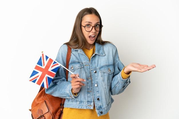 Giovane donna ispanica che tiene una bandiera del regno unito sopra il muro bianco isolato con l'espressione di sorpresa mentre guarda il lato