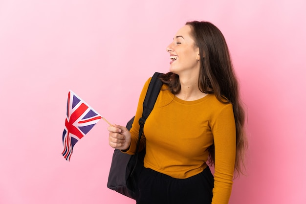 Giovane donna ispanica che tiene una bandiera del regno unito che ride in posizione laterale