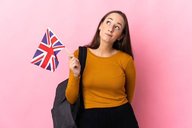 Giovane donna ispanica che tiene in mano una bandiera del regno unito e guarda in alto