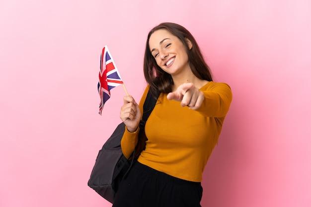 Giovane donna ispanica che tiene una bandiera del regno unito che punta davanti con espressione felice