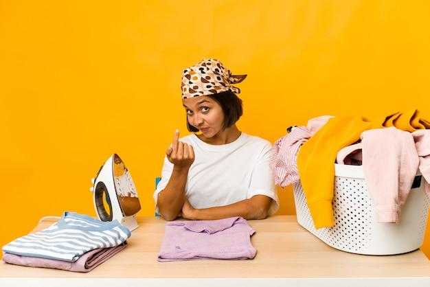 I vestiti di stiratura della giovane donna ispanica isolati puntano con il dito contro di voi come se invitando ad avvicinarsi.
