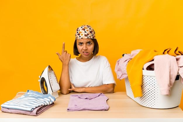 Vestiti rivestenti di ferro della giovane donna ispanica isolati che mostrano un gesto di delusione con l'indice.