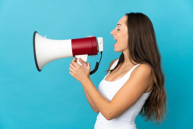Giovane donna ispanica su sfondo blu isolato che grida tramite un megafono per annunciare qualcosa in posizione laterale