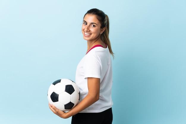 Giovane donna ispanica sopra la parete blu isolata con pallone da calcio
