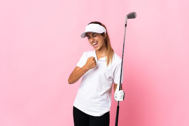 Giovane donna ispanica sopra il colore rosa isolato che gioca golf e che celebra una vittoria