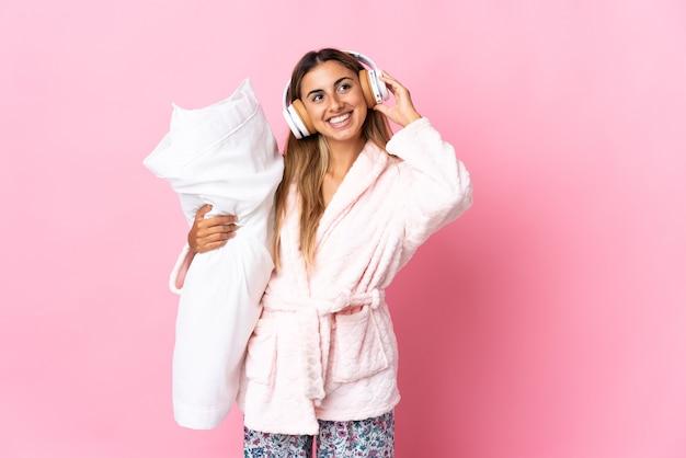 Giovane donna ispanica sopra la parete rosa isolata in pigiama e che tiene un cuscino e ascolta musica