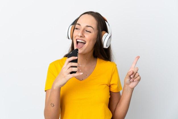 Giovane donna ispanica su sfondo bianco isolato ascoltando musica con un cellulare e cantando