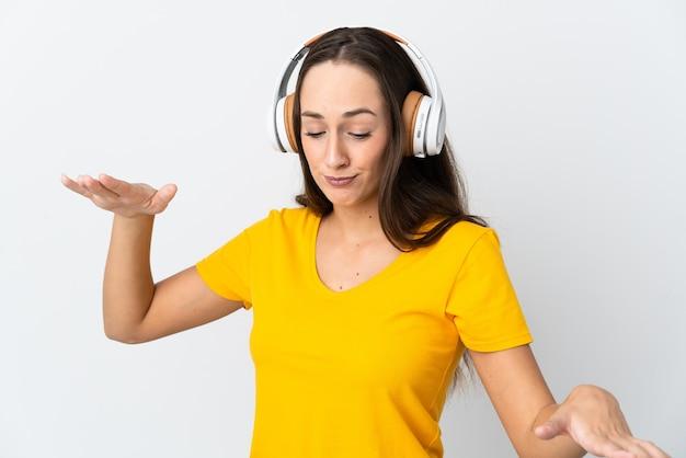 Giovane donna ispanica sopra la parete bianca isolata che ascolta musica e balli