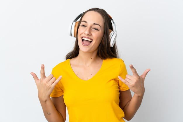Giovane donna ispanica sopra la musica d'ascolto della parete bianca isolata che fa il gesto della roccia