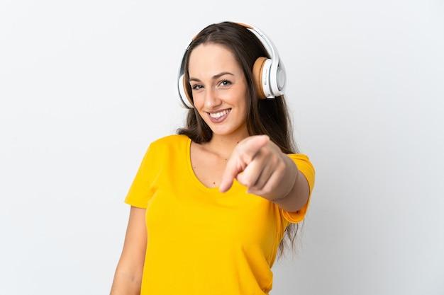 Giovane donna ispanica sopra la musica d'ascolto della parete bianca isolata e che indica la parte anteriore
