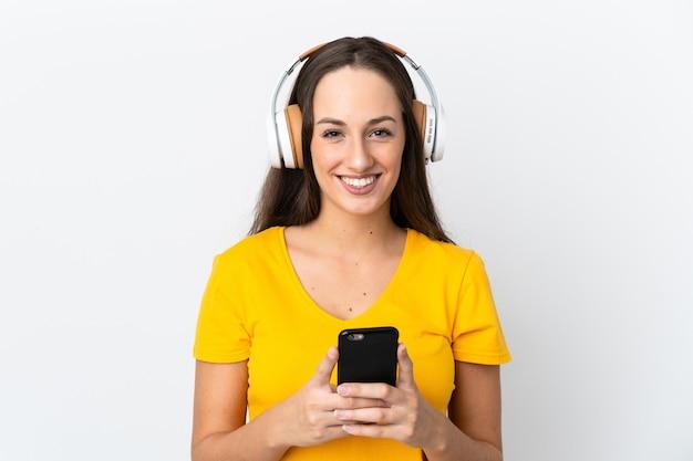 Giovane donna ispanica sopra la musica d'ascolto della parete bianca isolata con una parte anteriore mobile e di sguardo