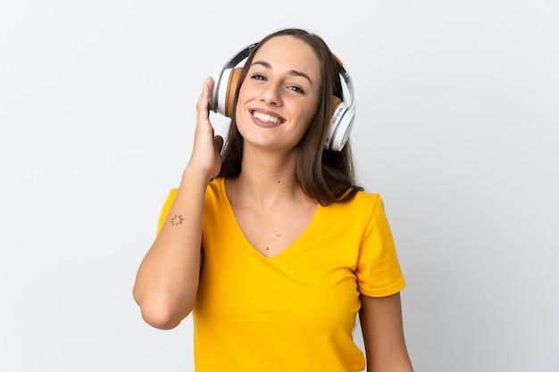 Giovane donna ispanica sopra la musica d'ascolto della parete bianca isolata