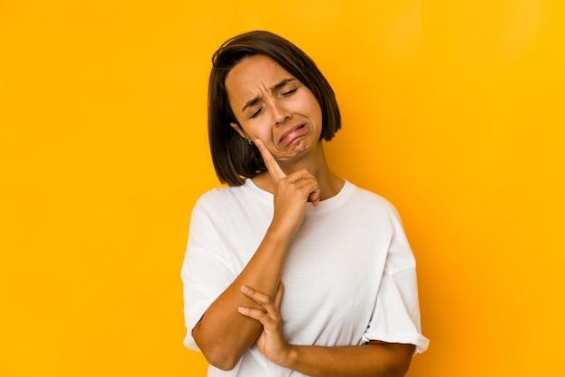 Giovane donna ispanica isolata sul pianto giallo, insoddisfatta di qualcosa, agonia e concetto di confusione.